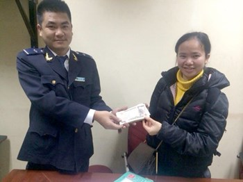 (L-R) Hanoi customs official Vu Quang Trung returns the money to Tran Thi Thanh Nga after it dropped from her luggage during a flight from Japan on December 22, 2014. Photo credit: VnExpress