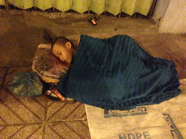 A child asleep on a sidewalk in Ho Chi Minh City.