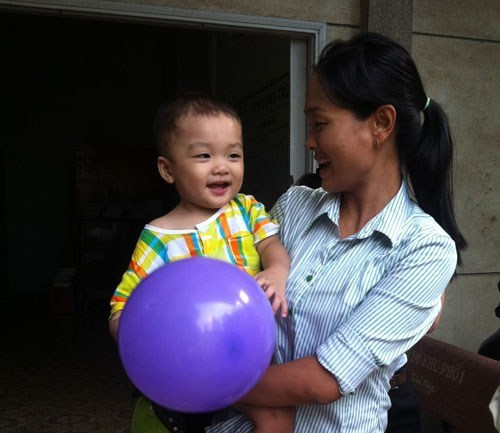 The boy who was abandoned in a Ho Chi Minh City taxi in early December. The employees of a ward office (pictured right) have been looking after him ever since. Photo: Ngoc Le