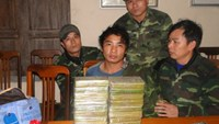 Nghe An border guards surround Ha Ba Cu (L, 2nd) and the 6.6 kilograms of heroin he was caught trafficking from Laos early on December 28, 2014. Photo: Viet Lam