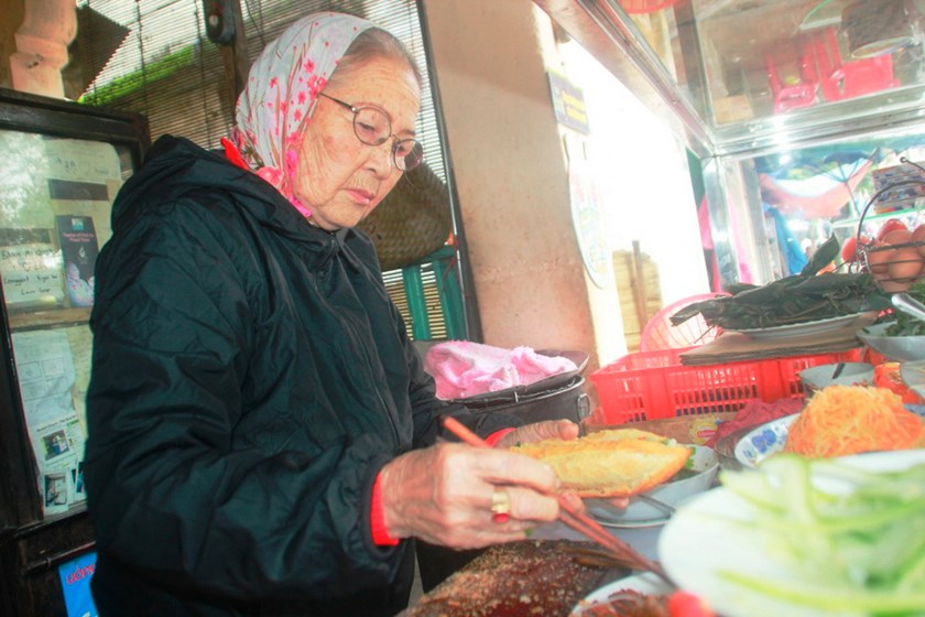 "Nguyen Thi Loc, dubbed as ""The Banh Mi Queen"", prepares a load of banh mi at her shop in Hoi An. Photo: Hoang Son"