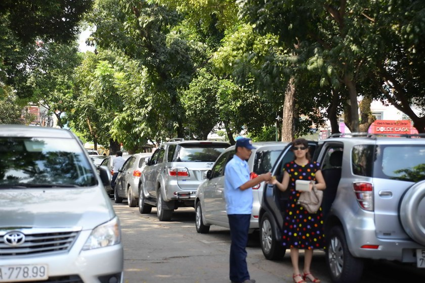 A woman pays parking fee to a guard at Le Van Tam Park where an underground parking lot project has been stalled for years due to red tape. Photo: Diep Duc Minh
