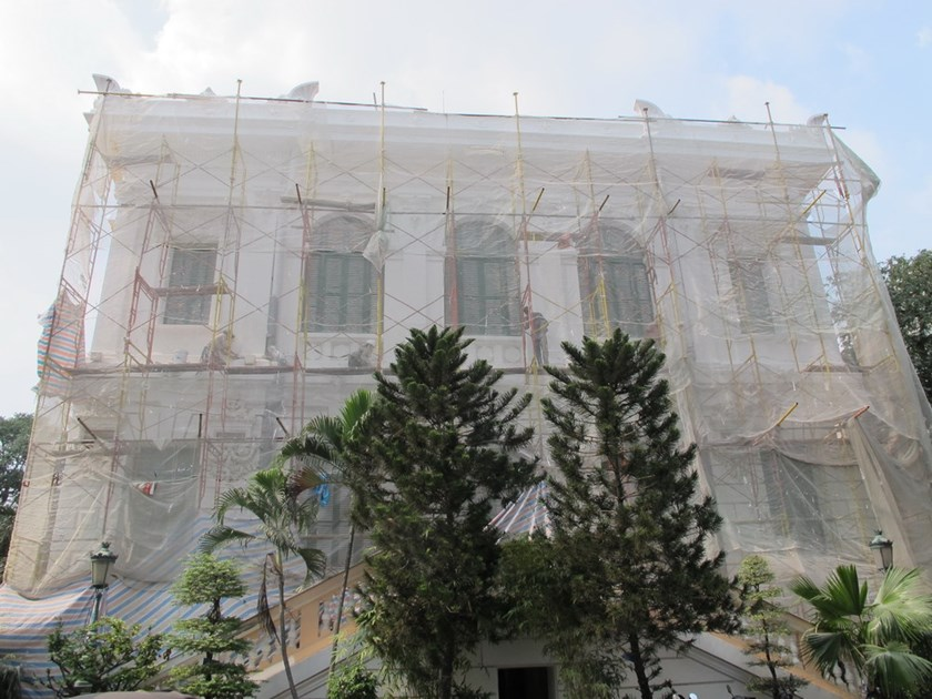 A portion of the Saigon Central Post Office was draped in mesh while its management board consults the city on a proper hue. Locals and tourists have criticized the office's choice of bright golden yellow as too bold and flashy. Photo: Le Cong Son