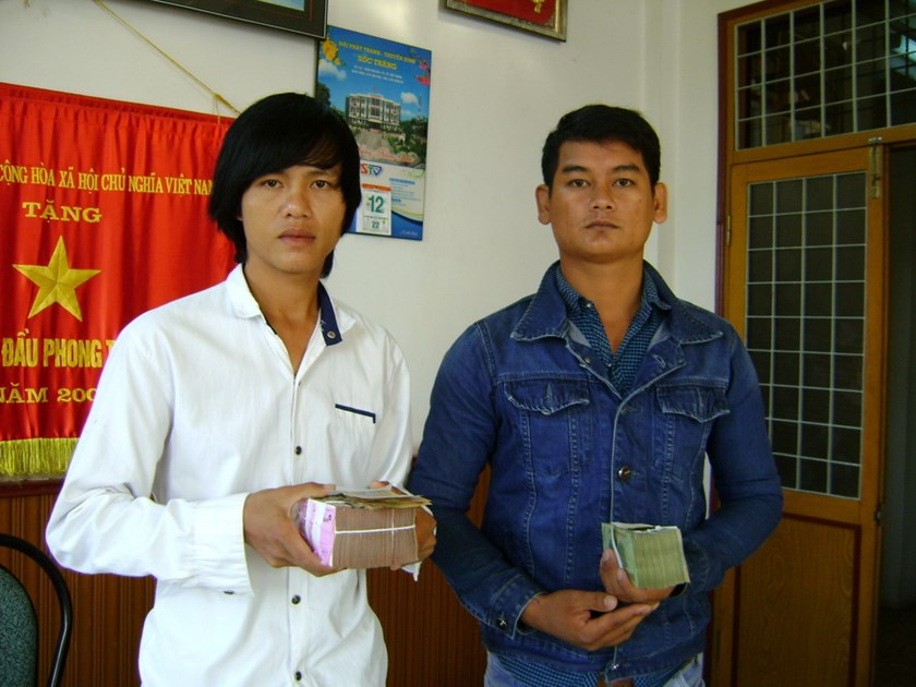 Tran Van Do (L) and Khau Soc receive compensation from Soc Trang prosecutors on January 14, 2015 after being falsely detained for murder in 2013. Photo: Huyen Trinh