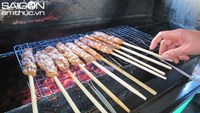Ground pork skewers being grilled over charcoal at a shop in Hue.