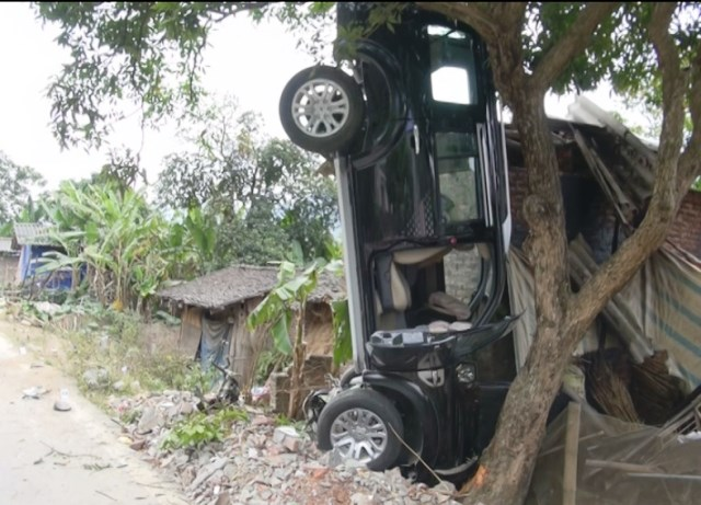 The car driven by an official from Cao Bang Province was flipped perpendicular to the ground after hitting a motorbike carrying three people on it on January 30, 2015. All three passengers died at the scene. Photo credit: Cao Bang Newspaper