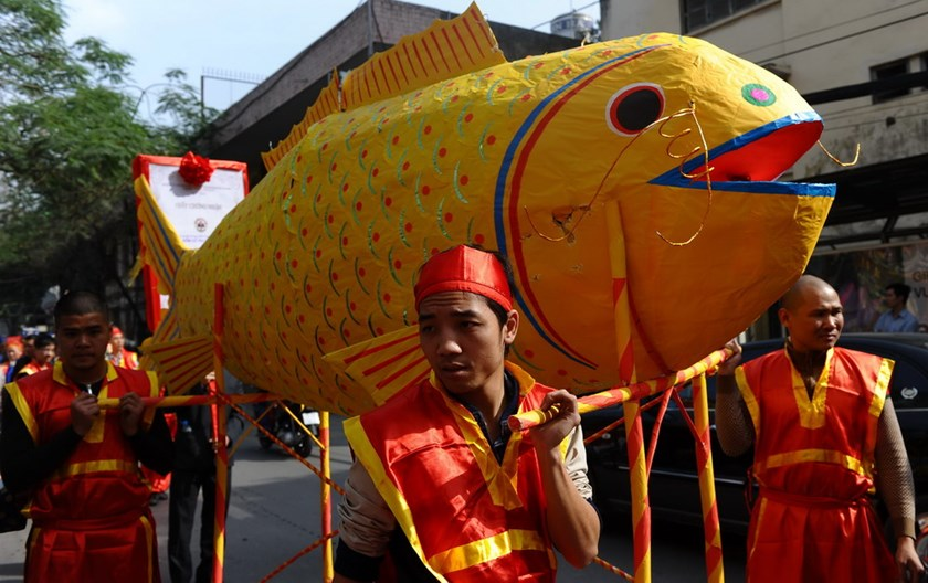 Villagers in festive dress carry a big paper-made carp they make to send Kitchen Gods to heaven during the Lunar New Year celeberations in Hanoi in 2013. Photo credit: AFP