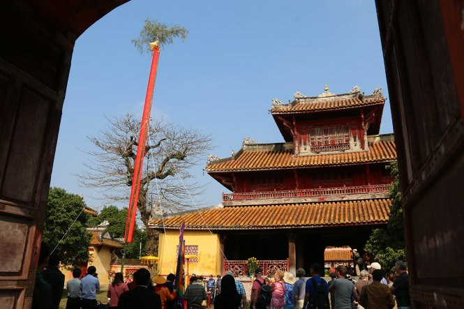 A bamboo pole which represents people's protection against devils during Tet was raised at Hue former citadel on February 11, 2015. Photo credit: Tuoi Tre