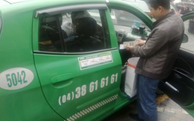 A passenger steps down a Mai Linh taxi cab. Photo credit: Tien Phong