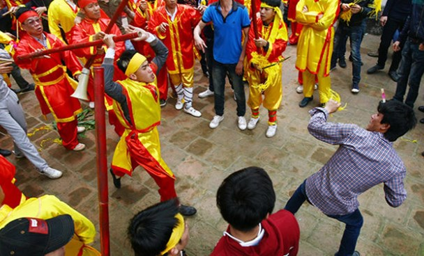 A member of Giong festival in Hanoi raises a cane to hit a man who tries to seize a piece of offering on parade on February 24, 2015. Photo credit: Tuoi Tre