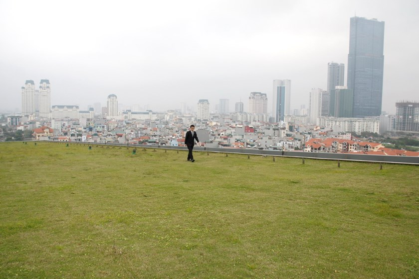 A man walks on a grass garden on the roof of a hotel in Hanoi. Photo: Le Quan