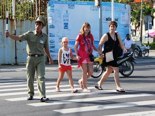 A volunteer helps tourists cross the road in Nha Trang. Photo: Nguyen Chung