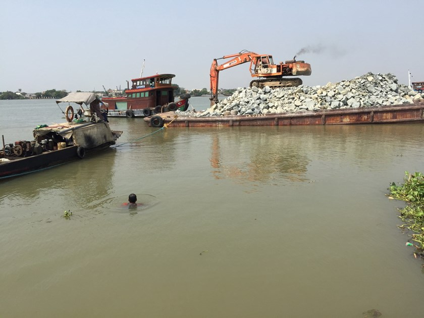 A crane is picking up rock on a barge to dump into the Dong Nai River, filling a large part of it to make ground for a real estate project. Photo: Dinh Son