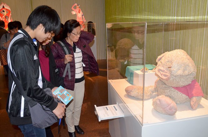 Visitors at a Hanoi exhibition of gay people's secrets look at one which contains a transgender's favorite teddy bear that her mother had cut and thrown into the street as not accepting that boys play pinky teddy bears. Photo credit: Tuoi Tre