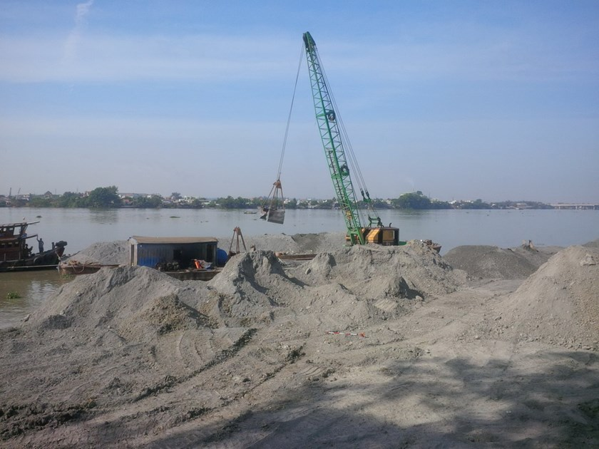 Materials are dumped into the Dong Nai River to fill a part of it for a development. Photo: Le Lam