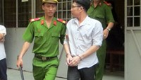 Police escort Nguyen Phu Hoa out of a trial in Ho Chi Minh City on March 19, 2015. He was sentenced to eight years for blackmailing. Photo credit: Tuoi Tre