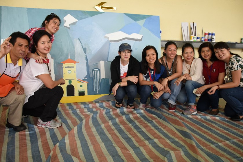 Staff members of US Consulate and artists in Ho Chi Minh City pose with an oil canvas of Ho Chi Minh City they created on March 18, 2015. File photo