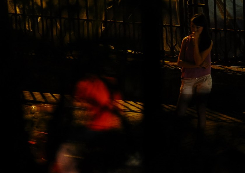 A prostitue waits for customers at night time on a street in downtown Hanoi in 2014. Photo credit: AFP