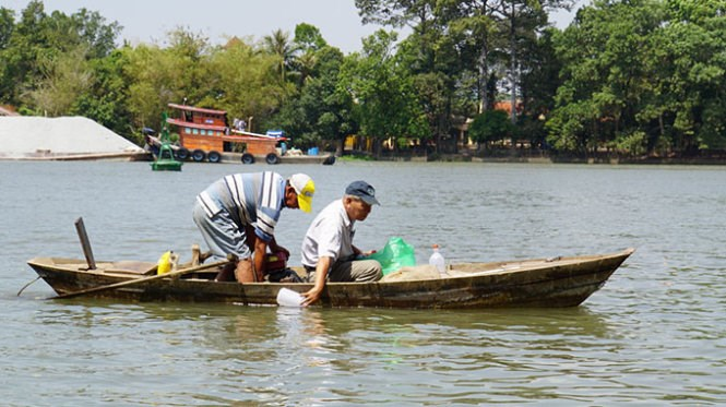 Researcher Pham Van Mien (R) with the Southern Institute of Ecology takes water samples from the Dong Nai River for testing. Photo credit: Tuoi Tre