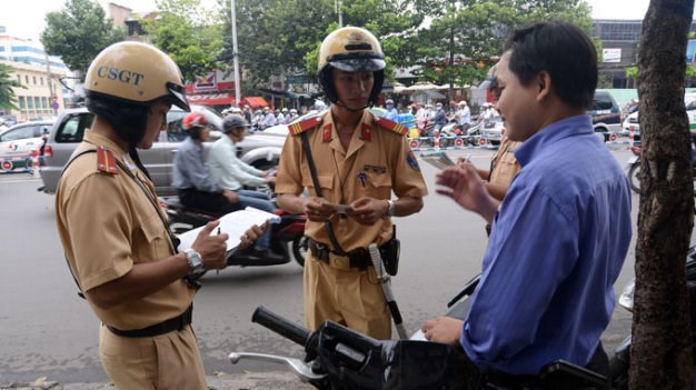 Traffic cops stop a motorist in Ho Chi Minh City. Photo credit: Tuoi Tre