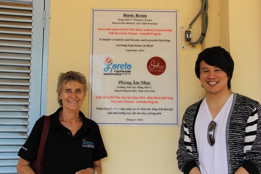 Loreto representative (L) with Thanh Bui outside the music room they opened together in Tra Vinh.