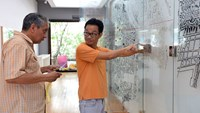 Tran Hoanh (R) and Archie Pizzini install a piece at their exhibition of Ho Chi Minh's daily architecture at a local exhibition which will last until May 2, 2015