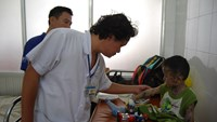 Doctor Truong Huu Khanh checks a boy covered in germicide for rashes at the Children's Hospital No.1 in Ho Chi Minh City. Photo: Thanh Tung