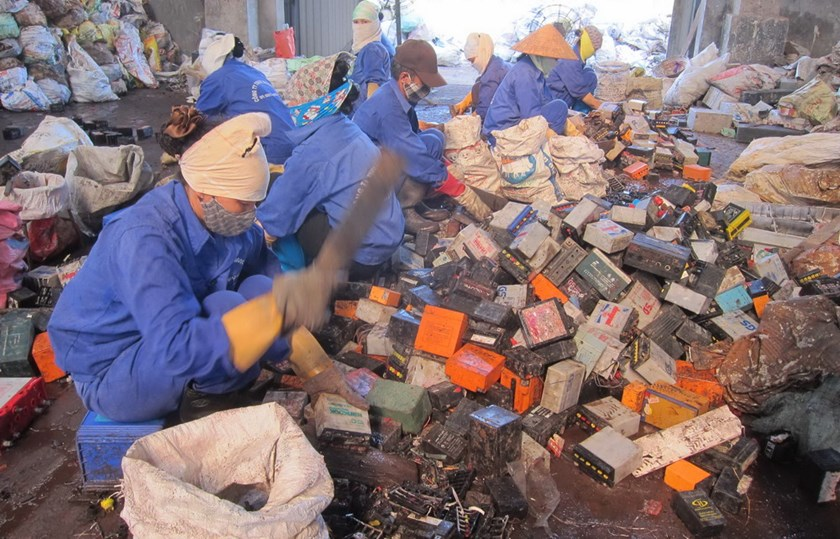 Workers smash batteries to take lead for resell at a commune in Hung Yen Province in northern Vietnam.
