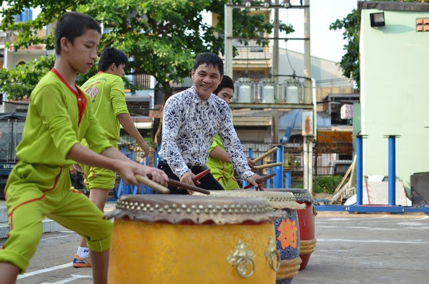 Luong Tan Hang (R) teaches a boy in his lion dance troupe how to hold and hit his drumsticks. Photo: Lam Ngoc