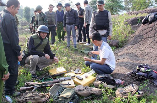 A photo provided by Son La Police shows officers checking the guns and bags of heroin left by smugglers from Laos on the night of May 3, 2015.