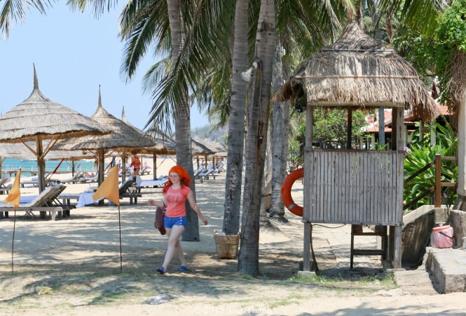 A tourist walks past a tent for guards of Ana Mandara resort at a beach in Nha Trang. She could only do after the city threatens to punish the resort for blocking the stretch from the public. Photo credit: Tuoi Tre