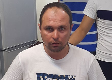 Asadchikh Serhiy at a Hanoi police station after he was arrested for using unauthentic cards to withdraw money from local ATMs. Photo credit: Dan Tri