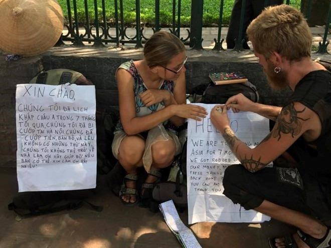 The foreign couple with notes asking for help in Hanoi. Photo credit: Zing