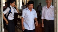Dinh Quang Dien (c) leaves a trial unhappy in Dak Lak Province May 21, 2015 as it only approved less than half of his compensation demand for an eight-month false custody. Photo credit: Tuoi Tre