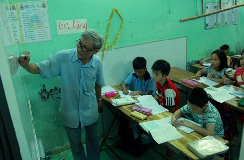 Doan Minh Hung with students in the free night class at his rent home in Ho Chi Minh City. Photo: Dinh Tuyen