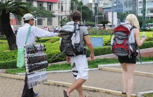 A street vendor follows two foreign tourists in Ho Chi Minh City downtown. Photo: Diep Duc Minh