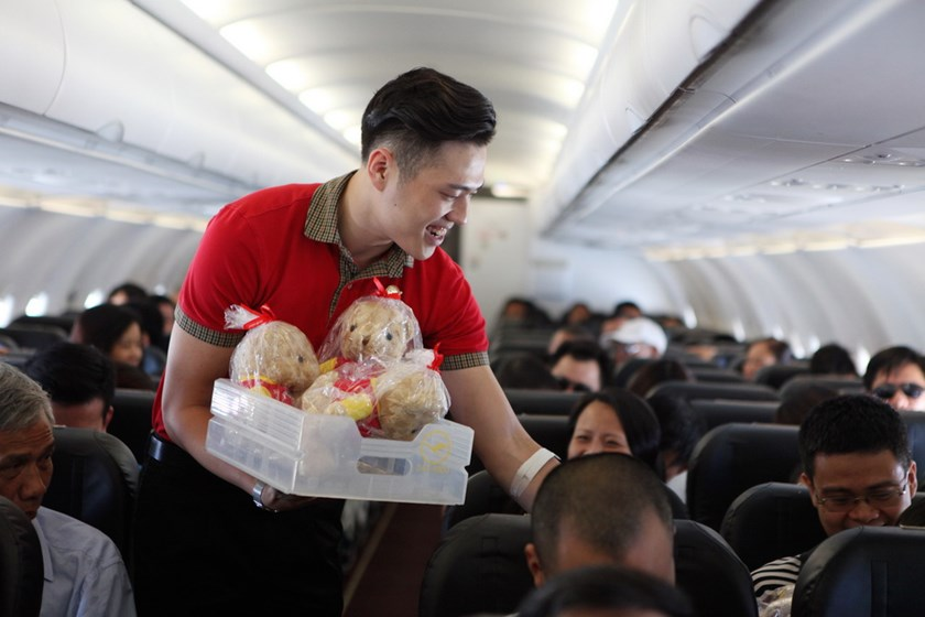 A Vietjet's flight attendant distributes gifts to passengers.