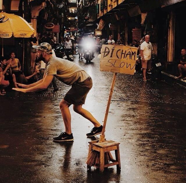A German man signals vehicles to slow down on the slippery Ta Hien street in Hanoi after the heavy rain on June 13, 2015, next to a sign he made with a local. File photo