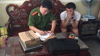 A police officer with 21-year-old Nguyen Van Do, one of the members in an e-commerce fraud busted in Ho Chi Minh City. Photo: Ngoc Le