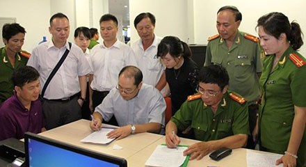 Yin Wen Sheng (L), a Chinese power official, watches as Vietnamese police and Chinese officials sign papers to bring him back to China to face a grand bribery probe. File photo