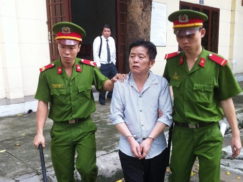 Police escort Chinese man Yan Jian Feng out of a trial in Ho Chi Minh City June 23, 2015. Photo: Ngoc Le