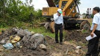 Tay Ninh officers check a site where a private hospital has buried its waste illegally. Photo credit: Tuoi Tre