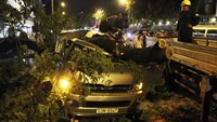 Workers clean up branches on a smashed car after a thunderstorm in Ho Chi Minh Wednesday night. Photo credit: VnExpress