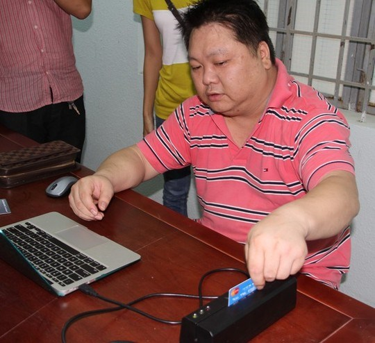 Yang Qing, 43, demonstrates his credit card trick to police in Khanh Hoa Province. Photo courtesy the police