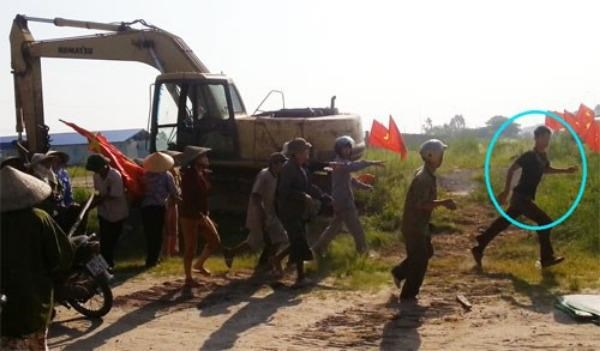 A scene from a video shows people chasing the driver of an excavator as he ran it over a woman during a land protest in Hai Duong on July 10, 2015.