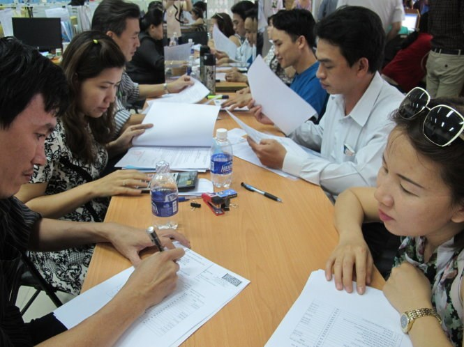 People fill in tax form at a local office. Photo credit: Tuoi Tre