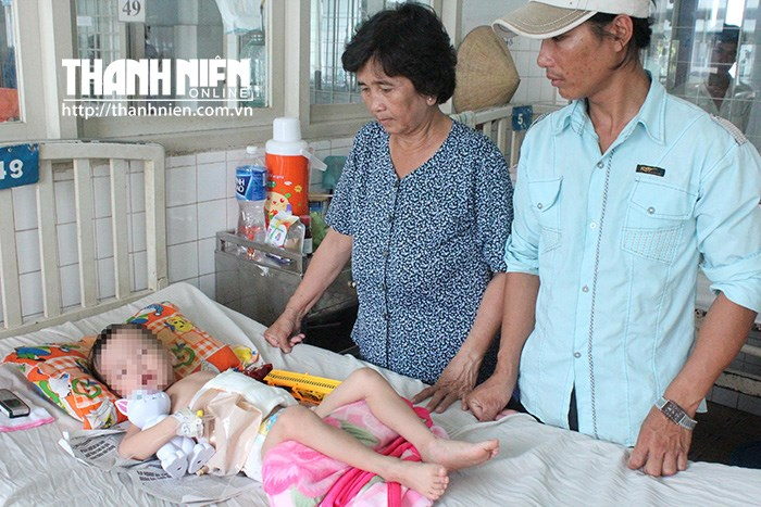 A 3-year-old boy is under treatment in Binh Duong Province for intestine rupture caused by his mother's boyfriend. His grandmother and father are taking care of him. Photo: Do Truong