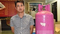 Nguyen Quoc Hung besides a gas cylinder that he and five others had hidden heroin in to smuggle to China. Photo: Hoang Trang
