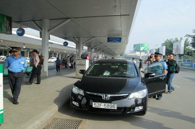 Traffic inspectors check an Uber car at Tan Son Nhat airport in Ho Chi Minh City. Photo credit: TBKTSG