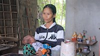 Len sits in her home in Quang Ngai Province with the fourth child she has with her husband, after he finished a jail term for heavily beating another child. Photo credit: Tuoi Tre